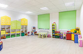 Light interior of a modern kindergarten in yellow and green colors. Panorama.