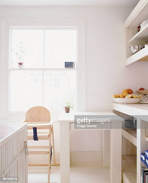 A bright kitchen with a high chair and dining table