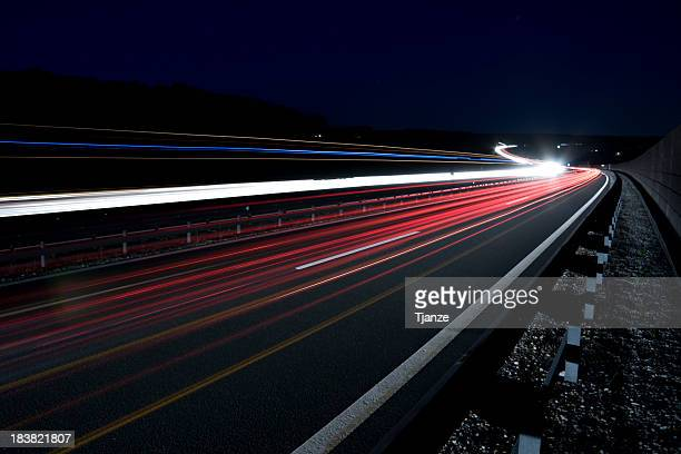 Bright light trails on the road in the dark
