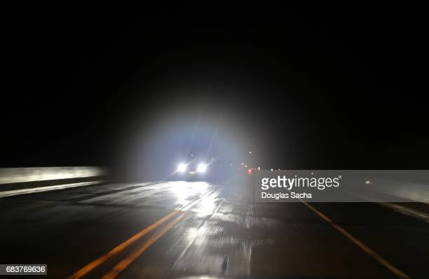 Bright lights from oncoming vehicle on a dark roadway