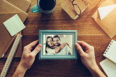 Close-up top view of man holding photograph of young couple over wooden desk with different chancellery stuff laying around