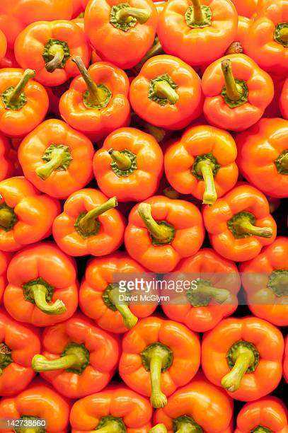 Bright orange bell peppers stacked neatly
