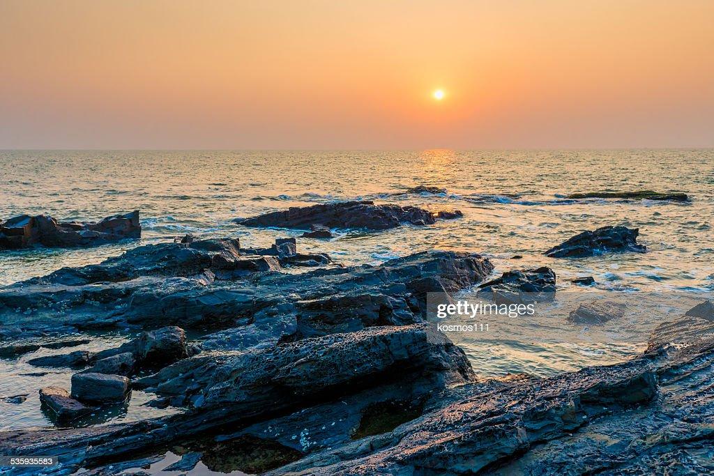 bright orange sun over the sea and rocky shore : Stock Photo
