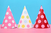 Bright party polka dot party hats on modern pink and blue background.