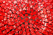 Part of a vivid red circular mosaic with some white speckles  in an overhead view for use as a background or texture.