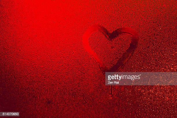 Bright Red Heart Symbol of Love on window covered with water drops from condensation
