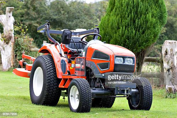 A bright red tractor on green grass