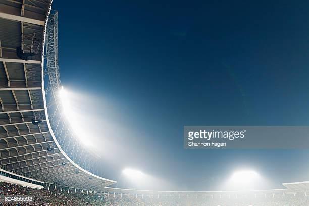 Bright stadium lights against a dusk sky
