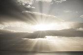 Bright sun and sun rays shining through dark stormy rain clouds onto the sea.
