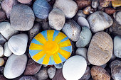 Bright sun painted on pebble with stones background.