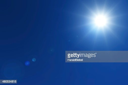 Bright sun with lens flares on deep blue sky : Stock Photo
