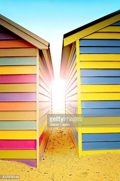 Bright sunlight between beach huts