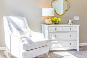 Bright white modern rocking chair in nursery room with chest of drawers, decorations in model staging home, apartment or house