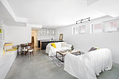Horizontal image of a bright white open plan living room and kitchen. Bachelors basement apartment. Space for copy.