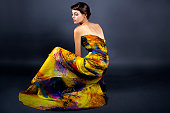 Woman modeling a yellow dress on a dark background for contrast.  She is wearing garment with a generic tie dye design.  The image is depicting the fashion industry and style.  The model is a caucasia