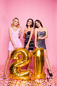 Brightful expressions of happy emotions of three amazing pretty astonished girls having fun  celebrating birthday party  21 years old in luxury dresses with golden baloons  standing over pink backgrou