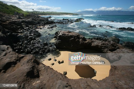 Brightly colored beach umbrella in a sandy circle surrounded by lava rock next to the ocean. : Stock Photo