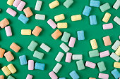 Brightly colored chewing gum laying flat  on green background