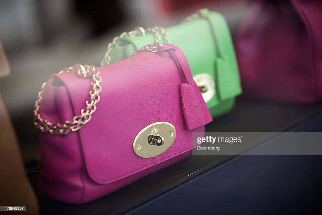 Brightly colored ladies handbags sits in the window display of a Mulberry Group Plc luxury store in London, U.K., on Thursday, March 20, 2014. Mulberry Group said Bruno Guillon will step down as chief executive officer after two years during which the British luxury handbag maker lost two-thirds of its market value. Photographer: Simon Dawson/Bloomberg via Getty Images