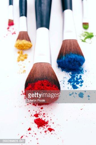 Brightly coloured eyeshadow powders on eyeshadow brushes, close-up : Stock Photo
