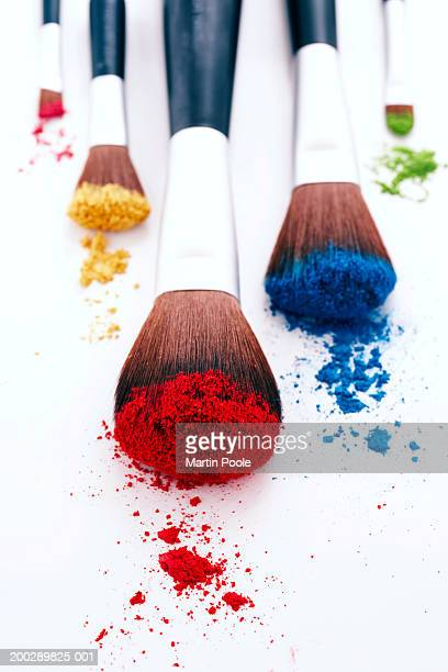 Brightly coloured eyeshadow powders on eyeshadow brushes, close-up