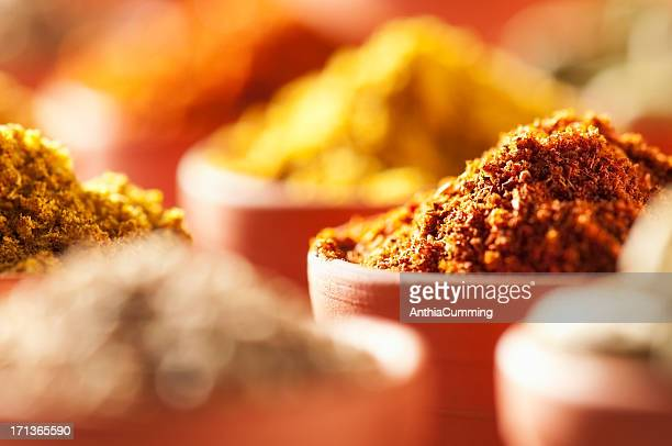 Brightly coloured ground cooking spices in terracotta bowls