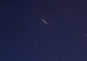A brightly coloured meteor can be seen as it streaks across the early morning sky on August 13 2013 over Saltburn United Kingdom The Perseid Meteor...