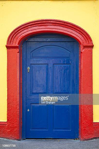 Brightly coloured red blue doorway yellow wall of Furlong's Bar in Passage East Co Waterford Ireland