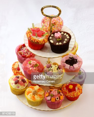 Brightly decorated cupcakes on tiered cake stand : Stock Photo
