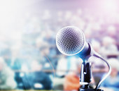 A vocal microphone is brightly lit in front of a defocussed audience on tiered seating who provide ample copy space.