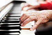 Brightly lit, a pair of old, arthritic, wrinkled hands play the piano.
