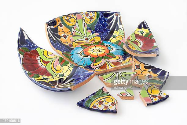 A brightly painted bowl in shards on a white background