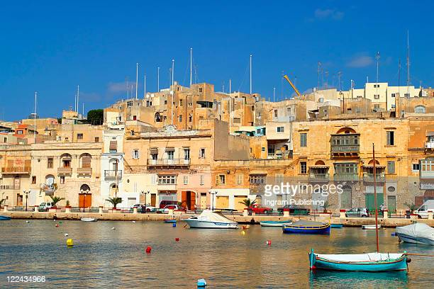 Brightly painted Maltese boats on blue water in summer, Malta.