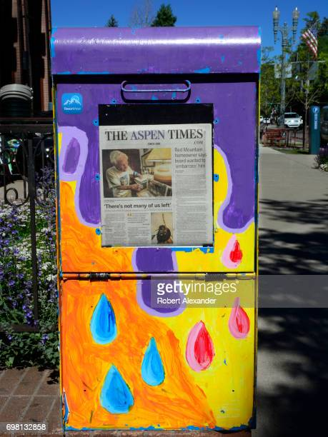 A brightlypainted newspaper distribution box holds copies of The Aspen Times a daily newspaper published in Aspen Colorado dating back to 1881