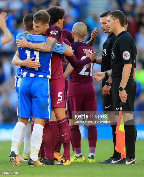 Brighton Hove Albion's Anthony Knockaert hugs Manchester City's John Stones after the final whistle during the Premier League match at the AMEX...