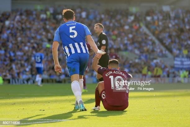 Brighton Hove Albion's Lewis Dunk helps up Manchester City's Sergio Aguero as he reacts after a missed chance during the Premier League match at the...