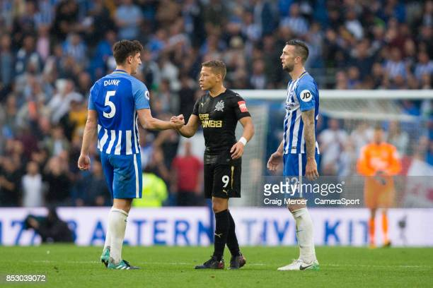 Brighton Hove Albion's Lewis Dunk shakes hands with Newcastle United's Dwight Gayle at full time during the Premier League match between Brighton and...