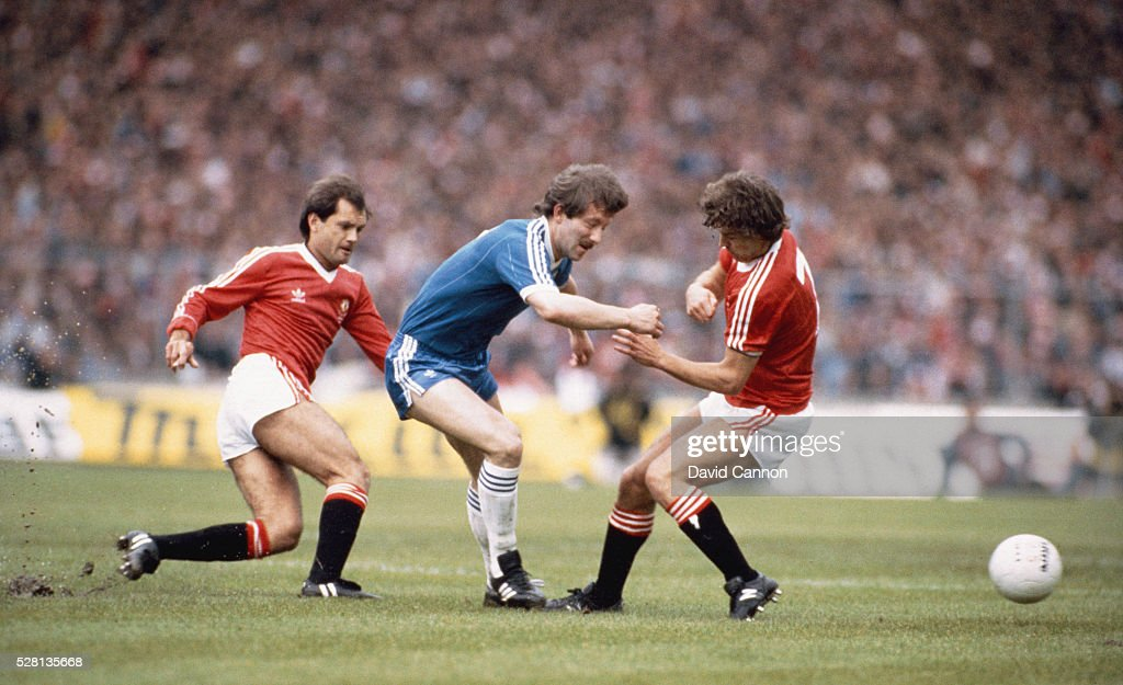 Brighton player Jimmy Case is tackled by Ray Wilkins (l) and Bryan Robson of Manchester United during the 1983 FA Cup Final at Wembley Stadium on May 21, 1983 in London, England.