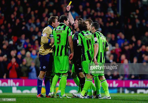 Brighton players surround referee Mick Russell as he shows a yellow card to Tomasz Kuszczak of Brighton after he conceded a penalty for a foul on...