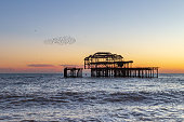 Sunset at Brighton Beach, with a Murmuration of Starlings Beside the Old West Pier