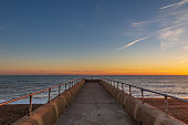 Looking down a jetty out to sea, with a sunset sky behind