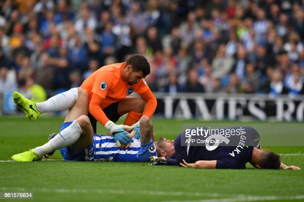 Brighton's Australian goalkeeper Mathew Ryan assists Brighton Irish defender Shane Duffy injured in a goal mouth clash as Everton's English defender...
