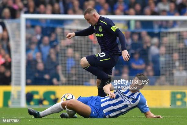Brighton's Dutch midfielder Davy Propper tackles Everton's English striker Wayne Rooney during the English Premier League football match between...