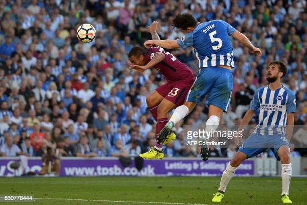 Brighton's English defender Lewis Dunk heads the ball into his own net under pressure from Manchester City's Brazilian striker Gabriel Jesus during...