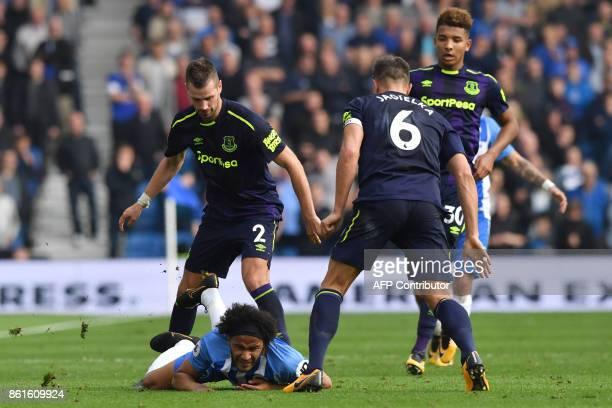 Brighton's English midfielder Izzy Brown is brought down by Everton's French midfielder Morgan Schneiderlin during the English Premier League...