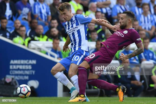 Brighton's English midfielder Solly March vies with Manchester City's Argentinian defender Nicolas Otamendi during the English Premier League...