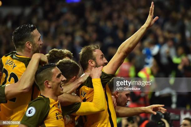 Brighton's English striker Glenn Murray celebrates with teammates after scoring their third goal from the penalty spot during the English Premier...