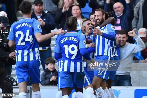 Brighton's English striker Glenn Murray celebrates with teammates after scoring Brighton's first goal during the English Premier League football...