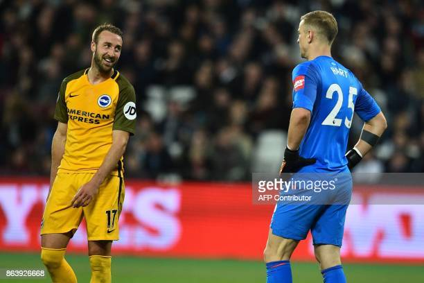 Brighton's English striker Glenn Murray smiles at West Ham United's English goalkeeper Joe Hart before scoring their third goal from the penalty spot...