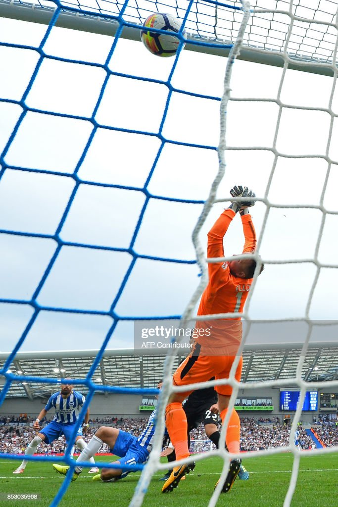 Brighton's Israeli striker Tomer Hemed (2nd L) scores the opening goal past Newcastle United's English-born Irish goalkeeper Rob Elliot (R) during the English Premier League football match between Brighton and Hove Albion and Newcastle United at the American Express Community Stadium in Brighton, southern England on September 24, 2017. Brighton won the game 1-0. / AFP PHOTO / Glyn KIRK / RESTRICTED TO EDITORIAL USE. No use with unauthorized audio, video, data, fixture lists, club/league logos or 'live' services. Online in-match use limited to 75 images, no video emulation. No use in betting, games or single club/league/player publications. /